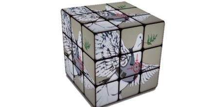 Rubik's cube puzzle with Banksy's street art of the dove of peace wearing a flak jacket with a target superimposed on it