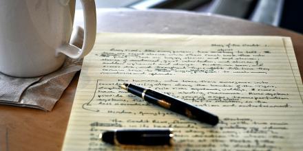 Still life image of mug, note pad and pen.