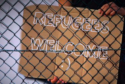 Woman behind bards holding sign that reads Refugees Welcome Image by kalhh from Pixabay