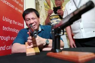Image of Filipino President Duterte looking down a gun barrel