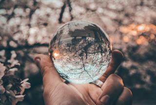 Hand holding glass-like globe