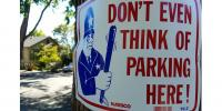 """Image: Sign with cartoon policeman holding truncheon and """"Don't Even Think of Parking Here"""" warning"""